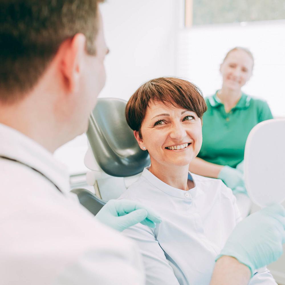 Frau lächelt dank Zahnfüllung aus Laupheim natürlich schön.