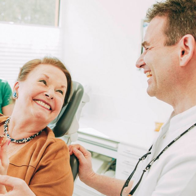 Patientin freut sich über sicheren Biss mit Zahnimplantaten aus Laupheim.