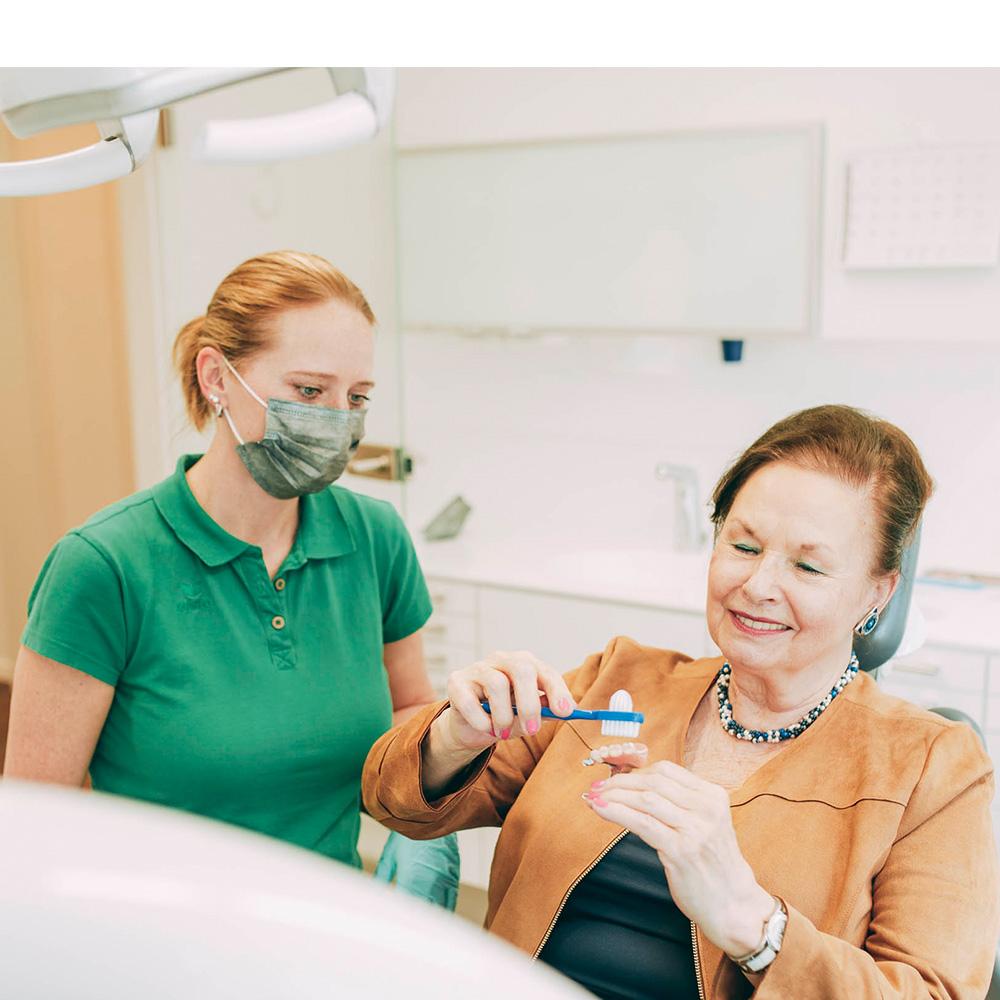 Mitarbeiterin zeigt Patienten, wie sie Zahnimplantate in Laupheim richtig reinigt.