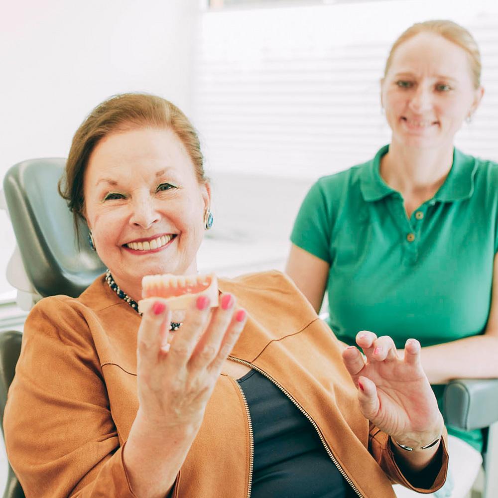 Patientin lächelt nach Behandlung mit Zahnimplantaten aus Laupheim.