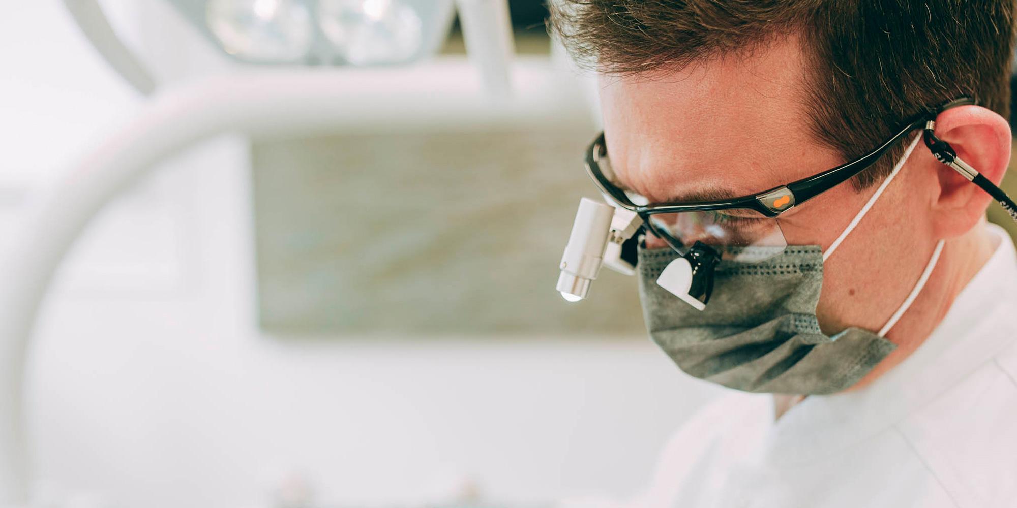 Zahnarzt mit Lupenbrille führt sicher und schonend Oralchirurgie in Laupheim durch.