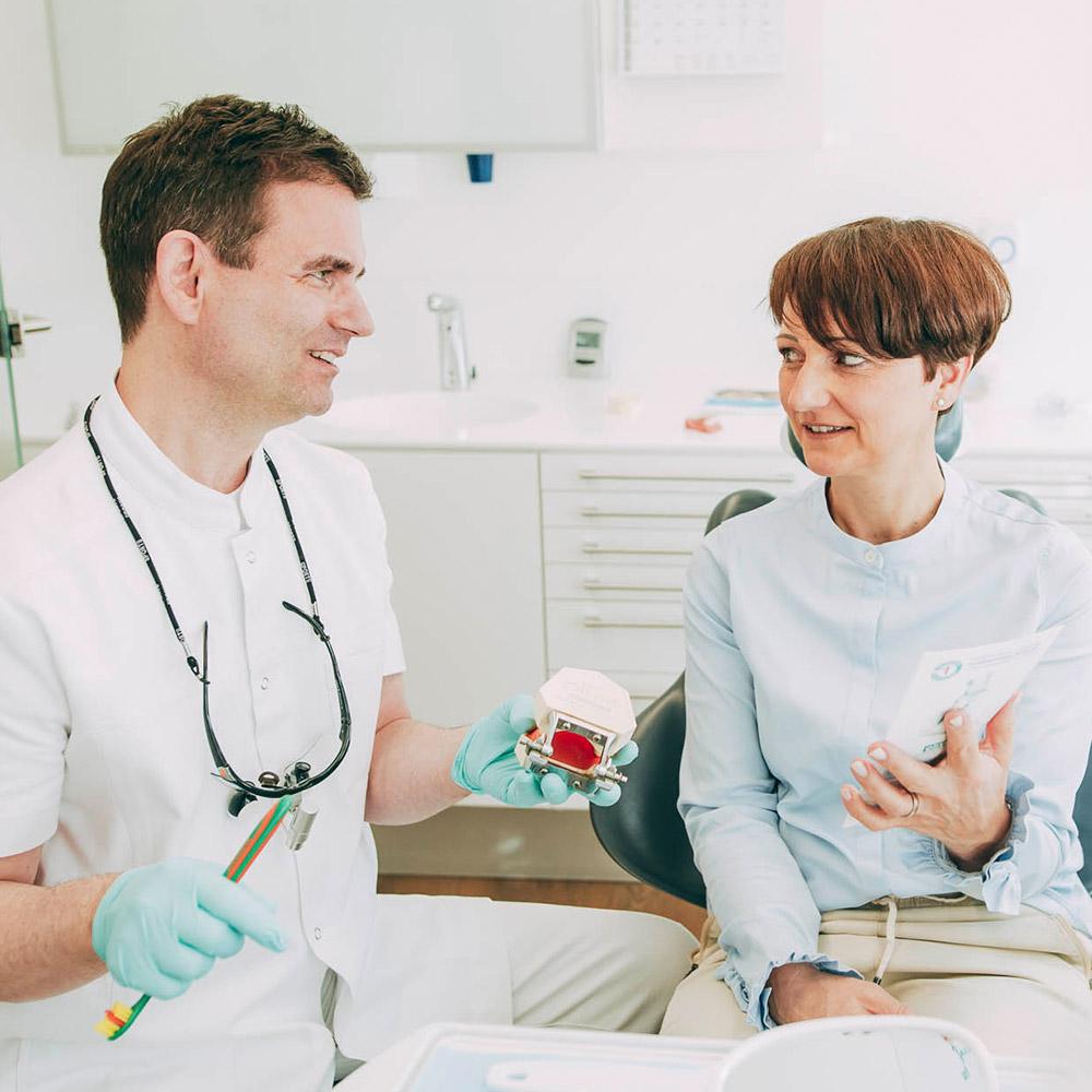Zahnarzt spricht mit Patientin über Parodontosebehandlung Laupheim.