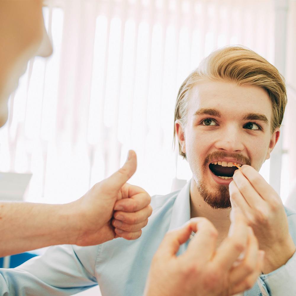 Zahnseide verwenden gehört zur Prophylaxe beim Zahnarzt in Laupheim.