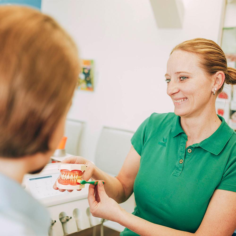 Mitarbeiterin erklärt Patientin Zahnputztechnik bei Prophylaxe Zahnarzt in Laupheim.