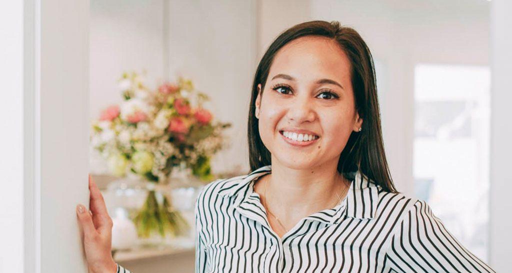 Junge Frau lächelt mit perfekten Zähnen nach Bleaching beim Zahnarzt Laupheim.