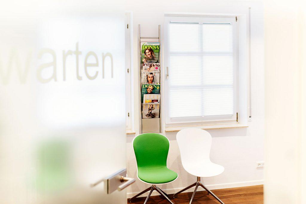 Grüne Stühle im gemütlichen Wartezimmer beim Zahnarzt Laupheim.