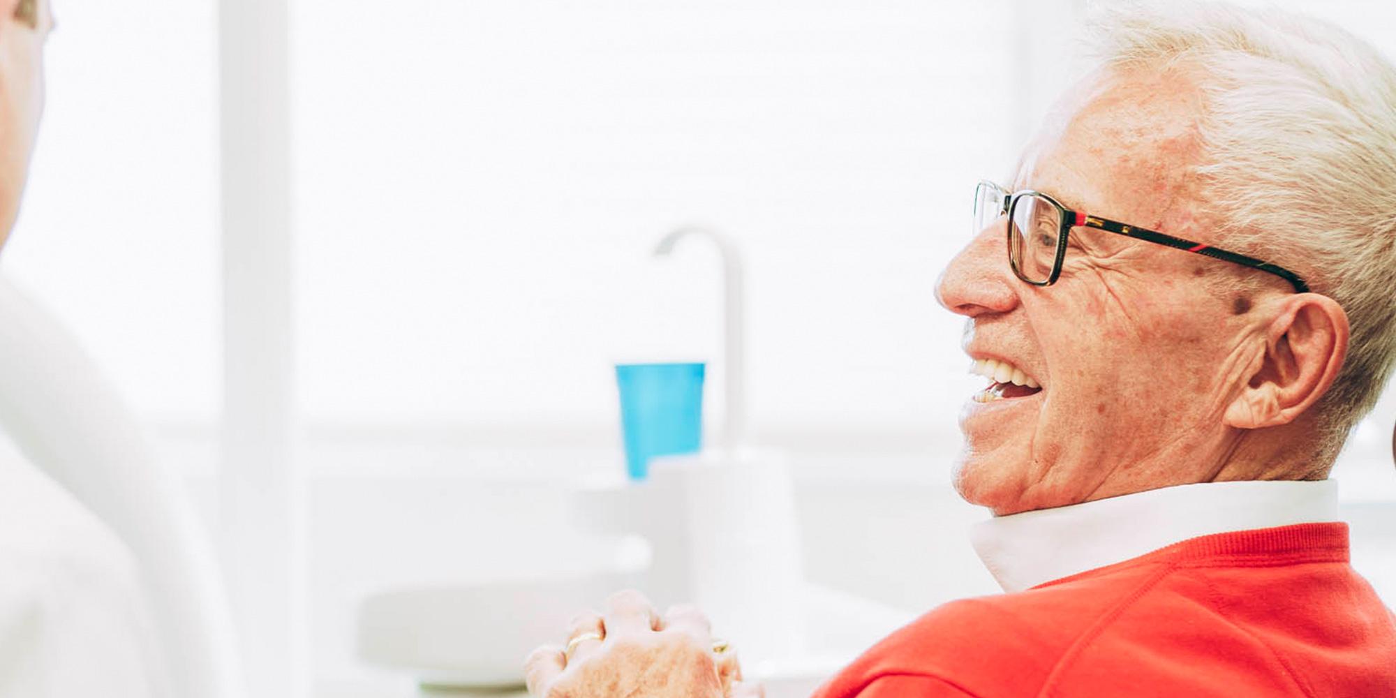 Senior lacht mit Brücken und Zahnprothesen aus Laupheim glücklich und zufrieden.